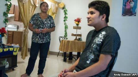 Ajuda Thapa, left, stands near her son, Jay Thapa, in their home in Burlington, Vermont.