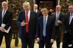 President-elect Donald Trump stands with Alibaba Executive Chairman Jack Ma as they walk to speak with reporters after a meeting at Trump Tower in New York, Jan. 9, 2017.