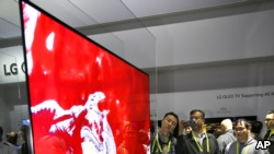 """IMAGE DISTRIBUTED FOR LG ELECTRONICS - CES 2017 attendees get their first glimpse of the LG SIGNATURE 77W7 OLED, the world's first ultra-thin Picture-On-Wall OLED TV, more popularly known as the """"Wallpaper TV"""" on Thursday, Jan. 5, 2017, in Las Vegas."""