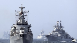 In this May 24, 2014 photo, China's Harbin (112) guided missile destroyer, left, and the DDG-139 Ningbo Sovremenny class Type-956EM destroyer, right, take part in a China-Russia 'Joint Sea-2014' navy exercise at the East China Sea off Shanghai, China.