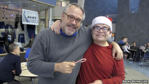 Alaska City Kindness Campaign - In this Dec. 20, 2016 photo, Thunder Mountain High School Principal Dan Larson, left, poses for photos with Mitchell Henderson, one of the students from Juneau-Douglas High School.