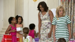 First lady Michelle Obama and Jill Biden visit with children as they make gifts for their mothers during their annual Mother's Day Tea to honor military-connected mothers at the White House in Washington, Friday, May 8, 2015. (AP Photo/Carolyn Kaster)