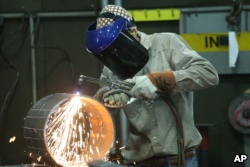 FILE - An employee welds pipe at Pioneer Pipe on Oct. 25, 2016 in Marietta, Ohio. The construction, maintenance and fabrication company employs around 800 people, supplying products to the oil and gas industry.