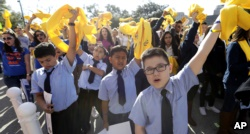 Students from St. Joseph Catholic School wave yellow scarfs during a rally in support of school choice on Jan. 24, 2017, in Austin, Texas.