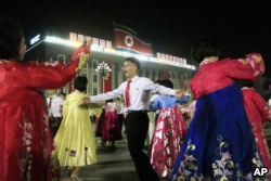 People dance in Kim Il Sung Square in Pyongyang, North Korea, Thursday, July 6, 2017, to celebrate the test launch of North Korea's first intercontinental ballistic missile two days earlier