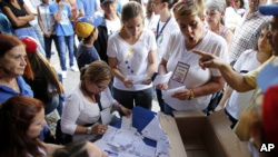 Volunteers count the ballots after the poll station closed during an unofficial referendum in Caracas, Venezuela, on Sunday, July 16, 2017.