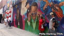 Spectators admire the new MuralsDC mural on the side of Ben's Chili Bowl.
