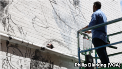 D.C. artist Aniekan Udofia works on his new mural for MuralsDC