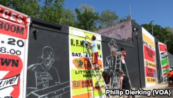 Cory Stowers (bottom right) and members of the ArtBloc organization work on a mural in Southeast D.C.