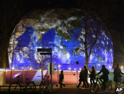 People pass the German pavilion in the shape of the earth during the COP 23 Fiji UN Climate Change Conference in Bonn, Germany, Wednesday evening, Nov. 15, 2017.