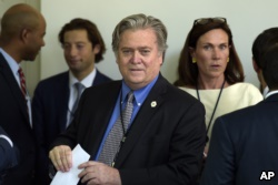 FILE - Stephen Bannon waits for President Donald Trump to make a statement about the U.S. role in the Paris climate change accord, June 1, 2017, in the Rose Garden of the White House.