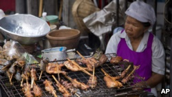 A street vendor cooks food on a street in central Bangkok, Thailand, Friday, April 22, 2016. In Bangkok, street food remains the heart and soul of local cuisine, sold day and night from carts and makeshift stands. (AP Photo/Mark Baker)