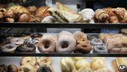 A selection of pastries, including doughnuts, bagels, rolls, croissants, turnovers and sticky buns are displayed in a New York coffee cart. (File Photo)