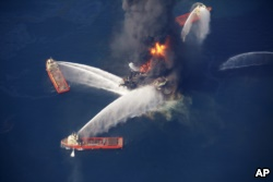 FILE - The Deepwater Horizon oil rig burns in the Gulf of Mexico, April 21, 2010, after an explosion that killed 11 workers and caused the worst offshore oil spill in the nation's history.