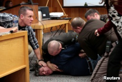 Eaton County sheriffs restrain Randall Margraves after he lunged at Larry Nassar, a former team USA Gymnastics doctor who pleaded guilty in November 2017 to sexual assault charges, during victim statements of his sentencing in the Eaton County Circuit Cou