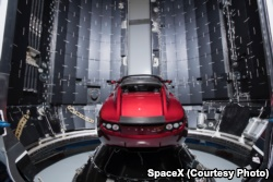This Dec 6, 2017 photo made available by SpaceX shows a Tesla car next to the fairing of a Falcon Heavy rocket in Cape Canaveral, Fla. For the Heavy's inaugural flight, the rocket will carry up Elon Musk's roadster. In addition to SpaceX, Musk runs the el