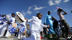 FILE - Young members of the Original Big Seven Junior Steppers dance during a second line at the New Orleans Jazz and Heritage Festival in New Orleans, Friday, May 5, 2017. (AP Photo/Gerald Herbert)