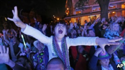 FILE - A young reveler scream for beads during the Krewe of Endymion Mardi Gras parade in New Orleans, Saturday, Feb. 25, 2017. (AP Photo/Gerald Herbert)