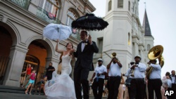 In this August 15, 2015, file photo, newlyweds dance their way out of St. Louis Cathedral at Jackson Square in the French Quarter of New Orleans. Catholic faith and traditions have played a role in New Orleans' culture since Feb. 9, 1718, when a priest plan