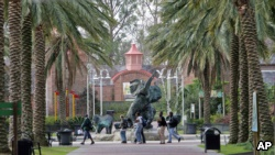 FILE - People walk past a bronze elephant on the grounds of the Audubon Zoo in New Orleans Tuesday Feb. 14, 2006. The Zoo is open only on weekends since Hurricane Katrina struck the city in August. (AP Photo/Bill Haber)