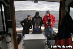 Artist Melinda Hunt, president of The Hart Island Project, left, and drone operator Parker Gyokeres, right, look over the video recorded by Daniel Herbert from the drone flight over Hart Island in New York.