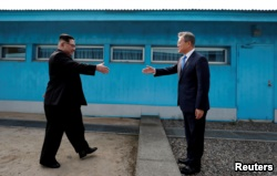 FILE - South Korean President Moon Jae-in and North Korean leader Kim Jong Un, left, are about to shake hands on their first meeting at the truce village of Panmunjom inside the demilitarized zone separating the two Koreas, South Korea, April 27, 2018.