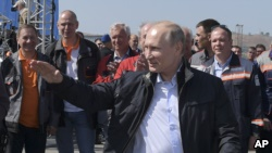 Russian President Vladimir Putin gestures while speaking to a group of workers after driving a truck to officially open the much-anticipated bridge linking Russia and the Crimean peninsula the opening ceremony near in Kerch, Crimea, Tuesday, May 15, 2018.