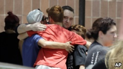 People react outside the unification center at the Alamo Gym, following a shooting at Santa Fe High School in Santa Fe, Texas.