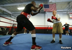 Parkinson's patient Jim Coppula works out in the ring with boxing coach Justice Smith (L) during his Rock Steady Boxing session in Costa Mesa, California September 16, 2013.