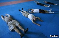 Parkinson's patients Jerry Held (L), Jim Coppula (2nd L) and Dan Cathcart (3rd L) stretch as they begin their workout at Rock Steady Boxing in Costa Mesa, California September 16, 2013.
