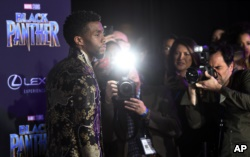 'Black Panther' actor Chadwick Boseman is surrounded by photographers as he poses at the premiere of the film at The Dolby Theatre on Monday, Jan. 29, 2018, in Los Angeles. (Photo by Chris Pizzello/Invision/AP)