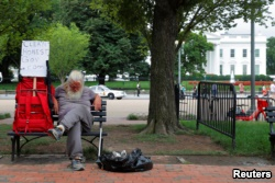 A homeless man sits outside the White House in Washington, U.S., August 2, 2018.