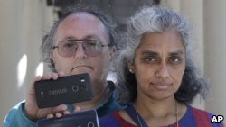 In this July 25, 2018 photo, Kalyanaraman Shankari, right, and her husband Thomas Raffill hold their phones while posing for photos in Mountain View, Calif. (AP Photo/Jeff Chiu)
