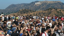A crowd gathers in front of the Hollywood sign at the Griffith Observatory to watch the solar eclipse in Los Angeles on Monday, Aug. 21, 2017. (AP Photo/Richard Vogel)