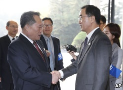 South Korean Unification Minister Cho Myoung-gyon, on the right, greets his North Korean counterpart Ri Son Gwon.