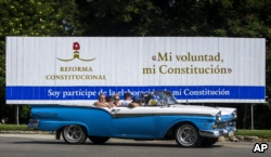 In this Oct. 2, 2018 photo, tourists take a joy ride in a vintage convertible car, past a billboard promoting constitutional reform