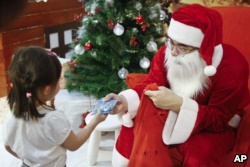A man dressed as Santa Claus gives a present to a child on Christmas day at a shopping mall in Petaling Jaya, Malaysia, Dec. 25, 2017.