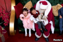 A girl laughs while her brother cries being held by Santa Claus at the King of Prussia Mall, in King of Prussia, Pennsylvania, U.S., December 8, 2018.
