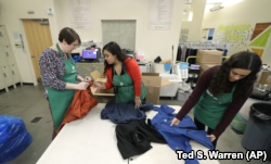 In this Friday, Dec. 21, 2018, photo, from left, Rebecca Schaechter, Nicole Herron and Rachel Herron fold and sort donated clothes at Treehouse, a nonprofit organization in Seattle that serves the needs of children in the foster-care system. The charity w