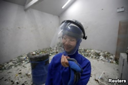 High school student Qiu Siyu, wearing protective gear, reacts after smashing wine bottles in an anger room in Beijing, China January 12, 2019. (REUTERS/Jason Lee)