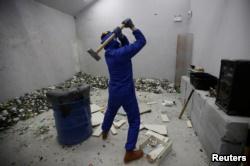 A customer wearing protective gear smashes old furniture with a hammer in an anger room in Beijing, China January 12, 2019. (REUTERS/Jason Lee)