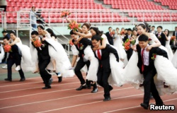 Couples take part in a competition during a mass wedding of 64 doctoral student couples at Harbin Institute of Technology, a university in Harbin, Heilongjiang province, China, June 4, 2017.