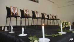 Framed photographs of seven crew members are displayed at a memorial service held by an association of Ethiopian airline pilots, in Addis Ababa, Ethiopia Monday, March 11, 2019. (AP Photo/Samuel Habtab)