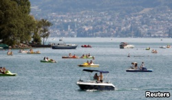 People on boats enjoy a hot summer day on Lake Zurich in Zurich, Switzerland