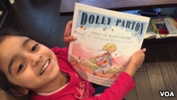 DC resident Jasmine Panchal, four, shows off her latest Books from Birth selection. (J.Taboh, VOA)