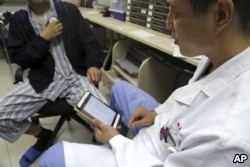 Dr. Li Dianyou uses a tablet computer to adjust the settings of a deep brain stimulation device implanted in the brain of a methamphetamine user named Yan, left, on Monday, Oct. 29, 2018, at Ruijin Hospital in Shanghai, China.
