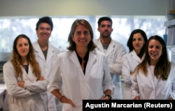 Marina Simian, a medical researcher, poses for a picture with members of her team May 9, 2019. (REUTERS/Agustin Marcarian)