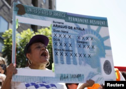 FILE - A woman holds a replica green card sign during a protest march to demand immigration reform in Hollywood, Los Angeles, California, October 5, 2013. (REUTERS/Lucy Nicholson)