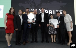 Representatives from onebillion, Jamie Stuart, third from left, and Andrew Ashe, fourth from left, and representatives from KitKit School, Sooinn Lee, third from right, and Gunho Lee, second from right, receive the XPRIZE Children's Literacy award.