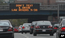 In this photo taken Friday, Sept. 24, 2010, a sign over the Massachusetts Turnpike in Boston alerts motorists to a new state law banning texting while driving. (AP Photo/Bill Sikes)
